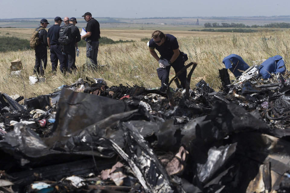 Photo - Australian experts examine the area of the Malaysia Airlines Flight 17 plane crash in the village of Hrabove, Donetsk region, eastern Ukraine Friday, Aug. 1, 2014. The investigators from the Netherlands and Australia plus officials with the Organization for Security and Cooperation in Europe traveled from the rebel-held city of Donetsk in 15 cars and a bus to the crash site outside the village of Hrabove. Then they started setting up a base to work from at a chicken farm. The investigative team's top priority is to recover human remains that have been rotting in midsummer heat of 90 degrees (32 degrees Celsius) since the plane went down on July 17.  (AP Photo/Dmitry Lovetsky)