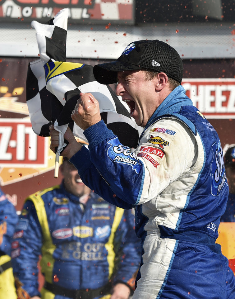 Photo - AJ Allmendinger waves the checkered flag as he celebrates in Victory Lane after winning a NASCAR Sprint Cup Series auto race at Watkins Glen International, Sunday, Aug. 10, 2014, in Watkins Glen, N.Y. (AP Photo/Derik Hamilton)