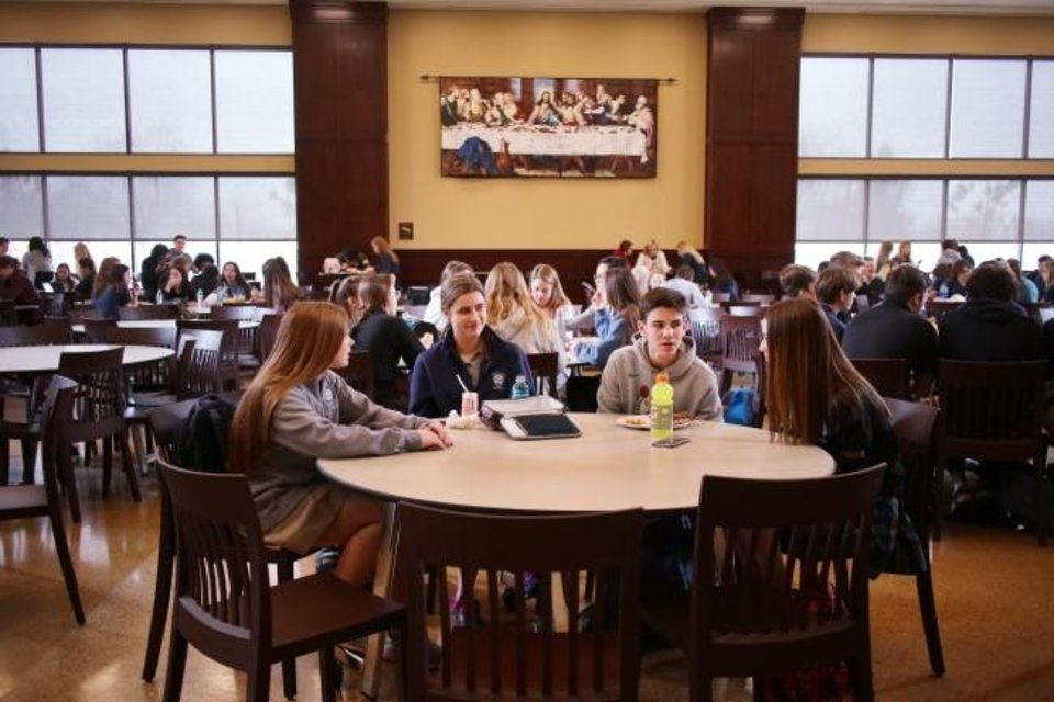 Photo -  Abagail Rogers, second from left, eats lunch with other students at Mount St. Mary High School. [Doug Hoke/The Oklahoman]