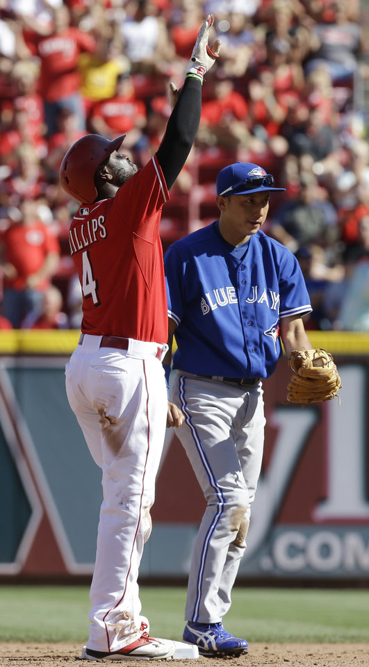 Photo - Cincinnati Reds' Brandon Phillips (4) points skyward after hitting a double off Toronto Blue Jays starting pitcher J.A. Happ to drive in a run in the fourth inning of a baseball game on Saturday, June 21, 2014, in Cincinnati. Blue Jays second baseman Munenori Kawasaki looks on. (AP Photo/Al Behrman)