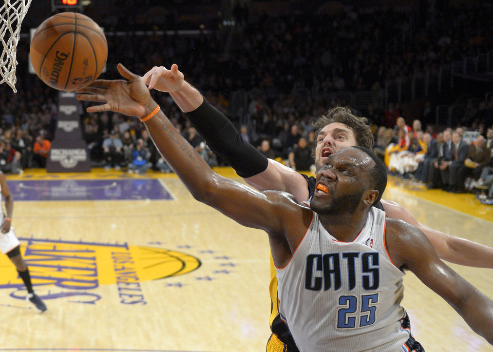 Photo - Charlotte Bobcats center Al Jefferson, right front, puts up a shot as Los Angeles Lakers center Pau Gasol, of Spain, defends during the first half of an NBA basketball game, Friday, Jan. 31, 2014, in Los Angeles. (AP Photo/Mark J. Terrill)