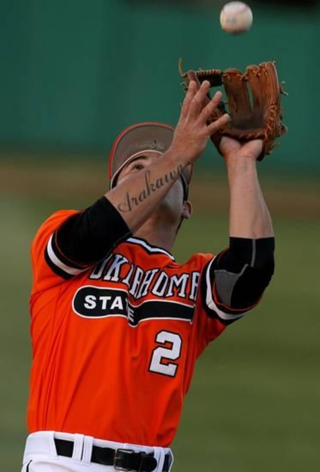 Photo - OSU's Tim Arakawa catches the ball for an out against OU on Tuesday night in Stillwater. Photo by Bryan Terry