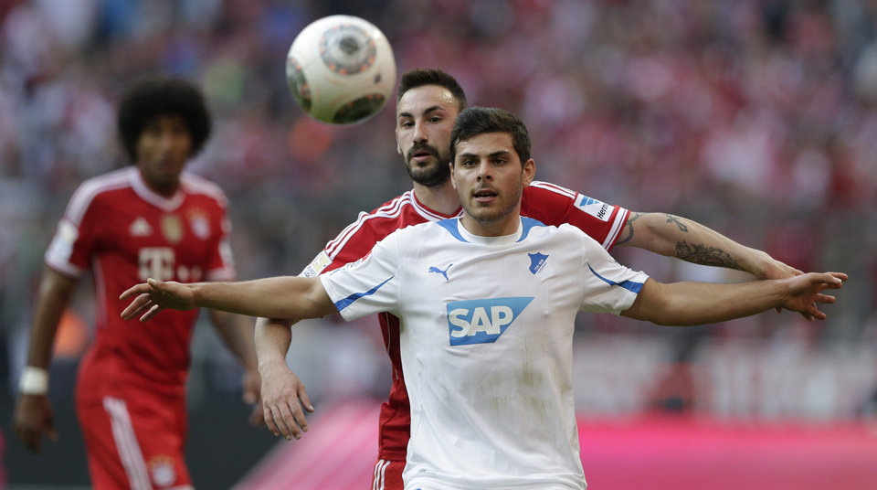 Photo - Hoffenheim's Kevin Volland, foreground, and Bayern's Diego Contento challenge for the ball during the German first division Bundesliga soccer match between FC Bayern Munich and TSG 1899 Hoffenheim, in Munich, southern Germany, Saturday, March 29, 2014. (AP Photo/Matthias Schrader)