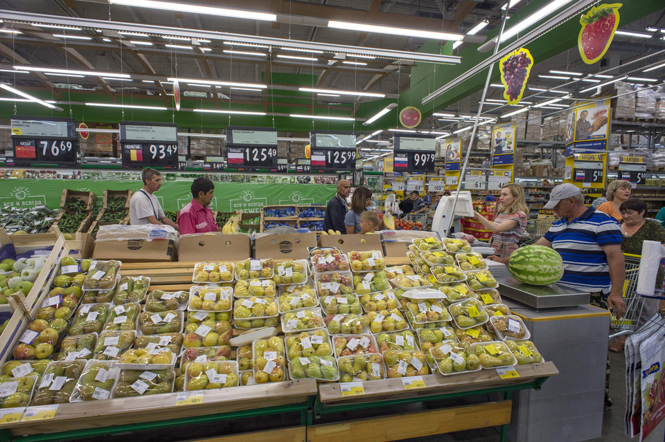 Photo - Customers look at shelves with imported fruit and vegetables at a supermarket in Novosibirsk, about 2,800 kilometers (1,750 miles) east of Moscow, Russia, Thursday, Aug. 7, 2014. Russia banned most food imports from the West on Thursday in retaliation for sanctions over Ukraine, an unexpectedly sweeping move that will cost farmers in North America, Europe and Australia billions of dollars but will also likely lead to empty shelves in Russian cities. (AP Photo/Ilnar Salakhiev)