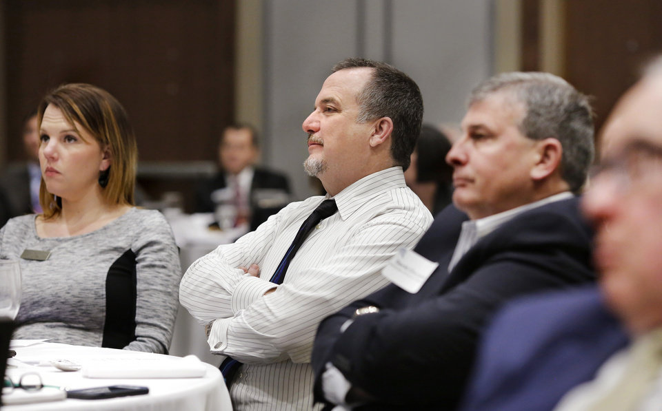 Photo -  Gina Britt, left, Mike Robberson, both with Kirkpatrick Bank, and David Chapman, a real estate investor and professor at the University of Central Oklahoma, listen to a presentation at the Edmond Economic Preview, sponsored by First Fidelity Bank, Thursday at the new Edmond Conference Center at Hilton Garden Inn. The Edmond Economic Development Authority organized the annual event. [PHOTO BY JIM BECKEL, THE OKLAHOMAN]
