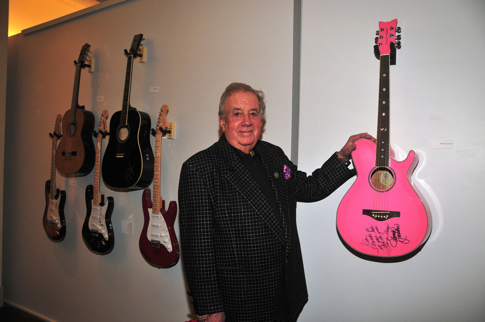 Photo - Music impresario Jim Halsey poses with Wanda Jackson's guitar at the January opening event for the exhibit