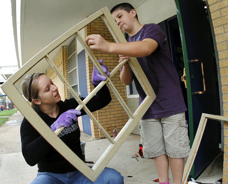 Photo - Lexi Skaggs, left, and Ben Rayner remove shards of glass from an old window pane that will be recycled into an element of a window planter. Skaggs is a mentor at the school. She is with the Pacer Fitness Center. Ben is the son of the principal, Ruthie Rayner.