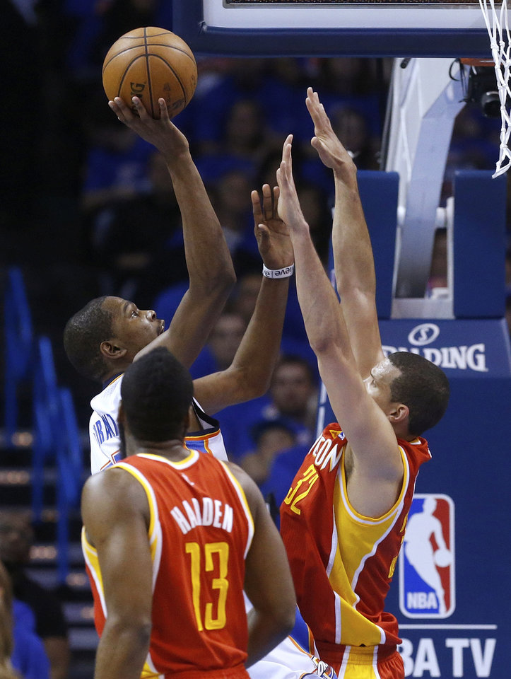 Oklahoma City Thunder forward Kevin Durant shoots in front of Houston Rockets guard James Harden (13) and forward Francisco Garcia (32) in the first quarter of Game 5 of a first-round NBA basketball playoff series in Oklahoma City, Wednesday, May 1, 2013. (AP Photo/Sue Ogrocki)