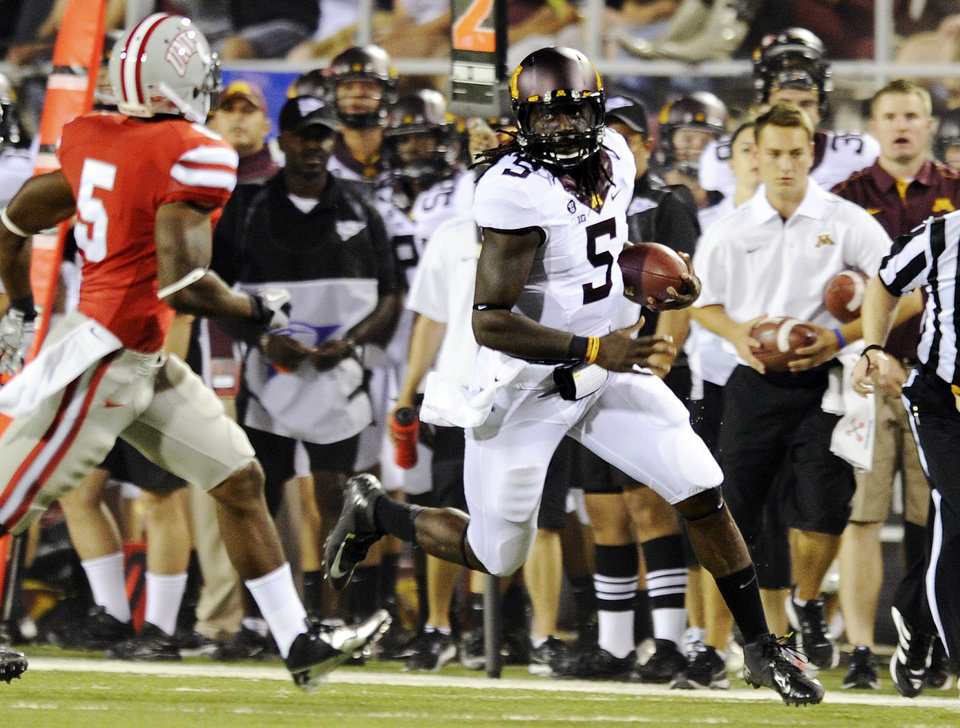 Photo -   Minnesota quarterback MarQueis Gray (5) looks to run past UNLV's Dre Crawford (5) during the first half of an NCAA college football game, Thursday, Aug. 30, 2012, in Las Vegas. (AP Photo/David Becker)