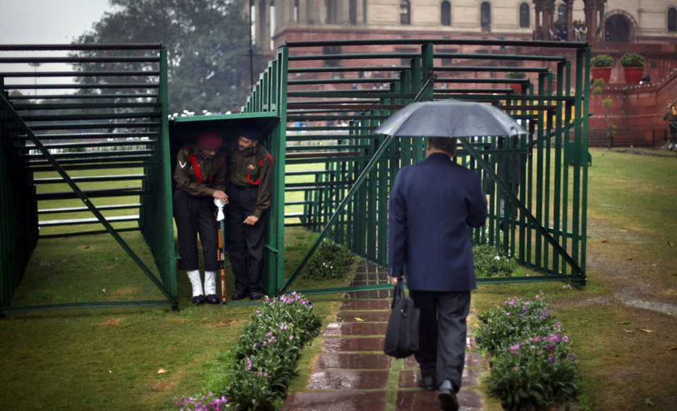 An Indian man walks past Indian security personnel taking shelter under temporary stands as it rains in New Delhi, India, Friday, Jan. 18, 2013. Heavy rains and hailstorm lashed the national capital, causing traffic jam and water logging in several areas. (AP Photo/Altaf Qadri)