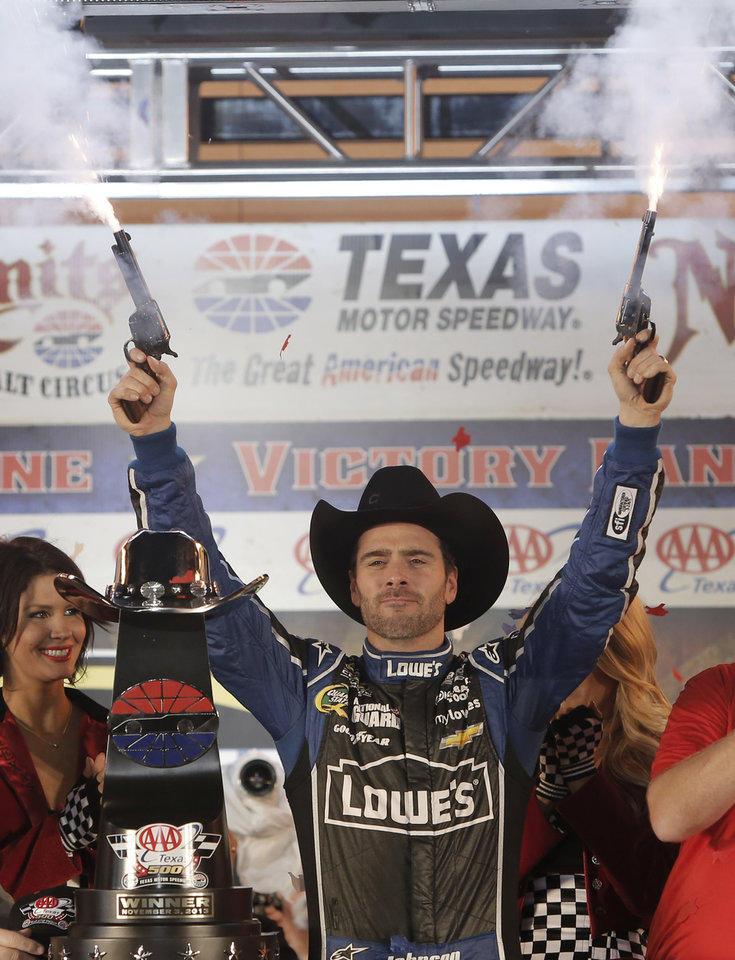 Photo - Jimmie Johnson fires pistols to celebrate winning the NASCAR Sprint Cup series auto race at Texas Motor Speedway in Fort Worth, Texas, Sunday, Nov. 3, 2013. (AP Photo/Brandon Wade)
