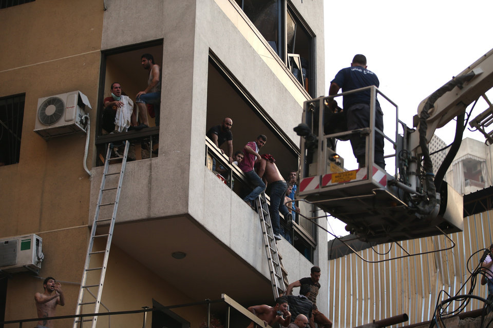 Photo - Lebanese citizens flee their house through a balcony at the site of a car bomb explosion in southern Beirut, Lebanon, Thursday, Aug. 15, 2013. The powerful car bomb ripped through a southern Beirut neighborhood that is a stronghold of the militant group Hezbollah on Thursday, killing people and trapping others in burning buildings, the media said. (AP Photo/Hussein Malla)