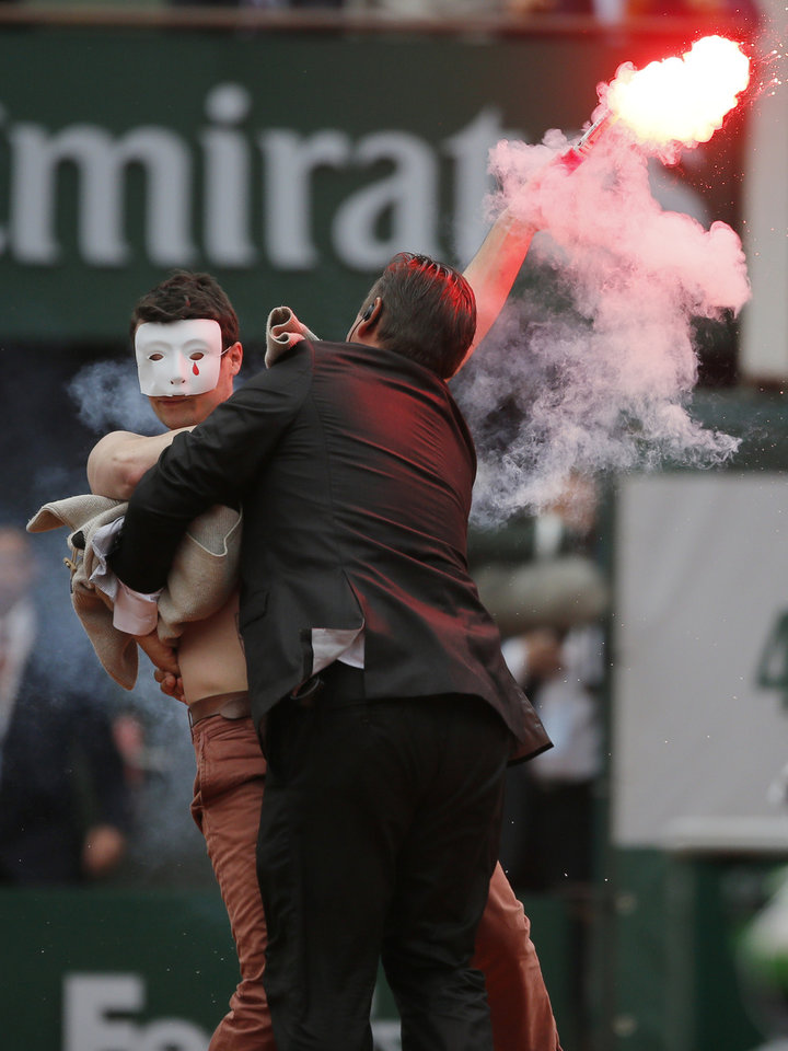Photo - A security guard grabs a demonstrator as Spain's Rafael Nadal plays against compatriot David Ferrer in the final of the French Open tennis tournament, at Roland Garros stadium in Paris, Sunday June 9, 2013. (AP Photo/Michel Spingler)