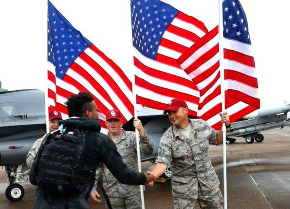 Photo - In a photo posted on Oklahoma basketball's official Twitter account, military veterans greet Oklahoma superstar Buddy Hield after the Sooners arrived in Houston on Wednesday.