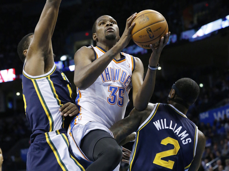 Oklahoma City Thunder forward Kevin Durant (35) shoots between Utah Jazz forward Derrick Favors, left, and forward Marvin Williams (2) in the first quarter of an NBA basketball game in Oklahoma City, Sunday, Nov. 24, 2013. (AP Photo/Sue Ogrocki)