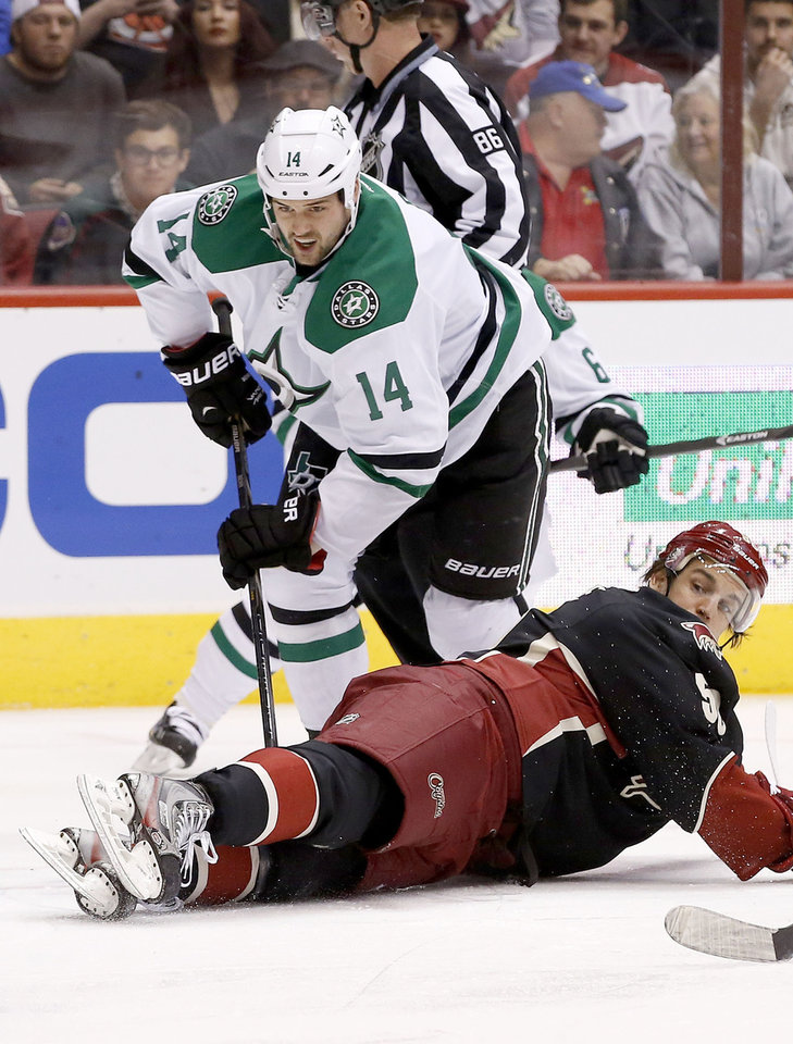 Photo - Phoenix Coyotes' Antoine Vermette, right, slides in front of Dallas Stars' Jamie Benn (14) to stop him from getting a shot off during the first period of an NHL hockey game, Tuesday, Feb. 4, 2014, in Glendale, Ariz. (AP Photo/Ross D. Franklin)