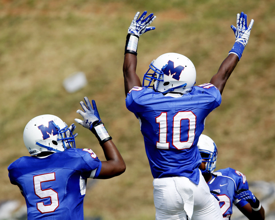 Photo - Teammates Alfonzo McMillian, #10, and Quincy Dotson, #5, celebrate in the end zone after McMillian's third quarter touchdown that put the Falcons ahead by  a score of 18-0 during the annual Soul Bowl football game  between the  Douglass Trojans and  the Millwood Falcons at Leodies Robinson Field in Oklahoma City on  Saturday, Sep. 14, 2013. In background is Andre Clanton, #22. Millwood defeated Douglass, 31-12.    Photo  by Jim Beckel, The Oklahoman.
