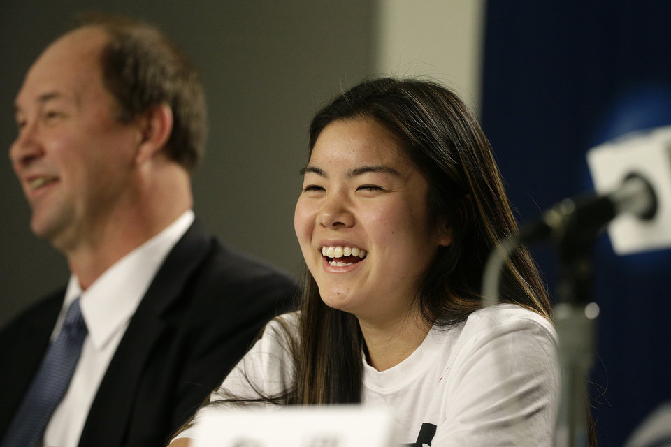 Photo - BYU's Kylie Maeda, right, laughs as she is joined by head coach Jeff Judkins during a news conference on Sunday, March 23, 2014, in Los Angeles. BYU is scheduled to play Nebraska in a second-round game of the NCAA women's college basketball tournament on Monday. (AP Photo/Jae C. Hong)