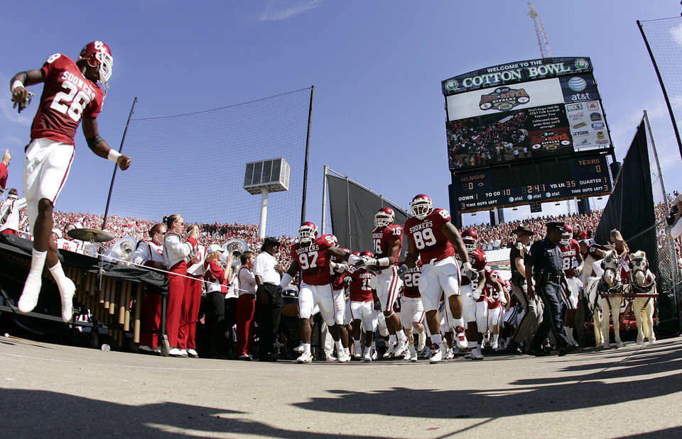 Photo - Oklahoma's Adrian Peterson (28) leads the Sooners out of the tunnel prior to the University of Oklahoma Sooners (OU) college football game against the University of Texas (UT), in the Red River Shootout at the Cotton Bowl, on Saturday, Oct. 7, 2006, in Dallas, Tex.     by Chris Landsberger, The Oklahoman  ORG XMIT: KOD