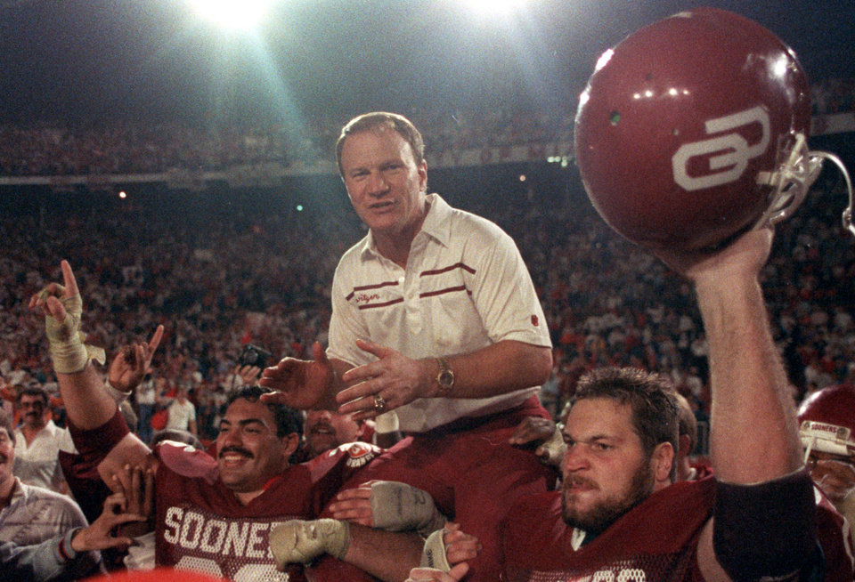 Photo - FILE - In this Jan. 2, 1986 file photo, University of Oklahoma (OU) Sooners coach Barry Switzer gets a ride from jubilant players Tony Casillas, left, and an unidentified player, right, following their win over Penn State in the Orange Bowl college football game in Miami, Fla. Twenty years later, Switzer says he no longer dwells on his tearful resignation as Oklahoma's football coach. The school had been hit by NCAA probation and player arrests. The resignation led to the Sooners' decade-long exile from college football's elite.  (AP Photo/Mark Foley, File) ORG XMIT: OKSO102