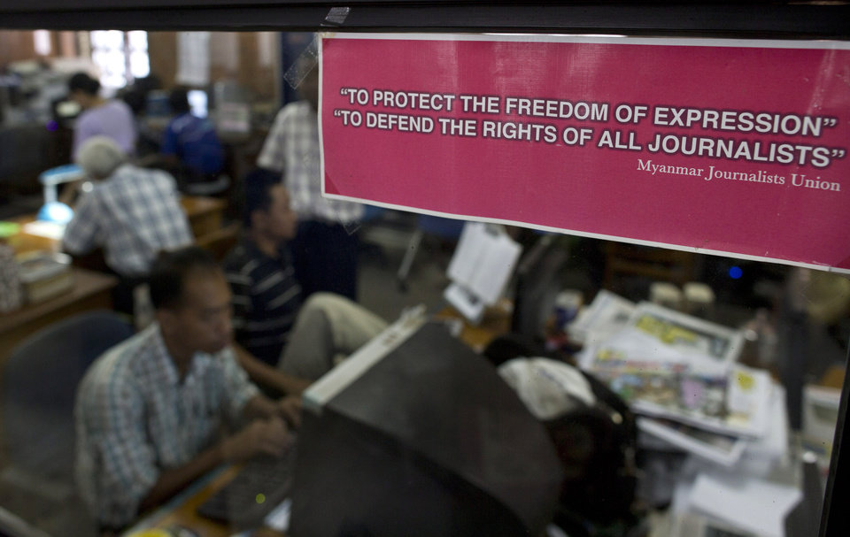 "In this March 14, 2013 photo, a memorandum of Myanmar Journalist Union displays as journalists work in the background in the newsroom of English weekly journal ""Myanmar Times"" in Yangon, Myanmar.  Myanmar journalists just getting used to their new era of freedom howled when the government announced plans for a media law that could lock many old restrictions back into place. Then, in the latest of many moves that never would have happened under the country's old military rulers, the government backed off. (AP Photo/Gemunu Amarasinghe)"