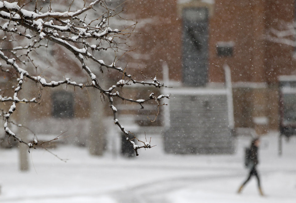 Photo - A woman walks on the campus of the University of Colorado as a blizzard dropped snow over Boulder, Colo., Wednesday Dec. 19, 2012. A storm that has dumped more than a foot of snow in the Rocky Mountains is heading east and is forecast to bring the first major winter storm of the season to the central plains and Midwest. (AP Photo/Brennan Linsley)