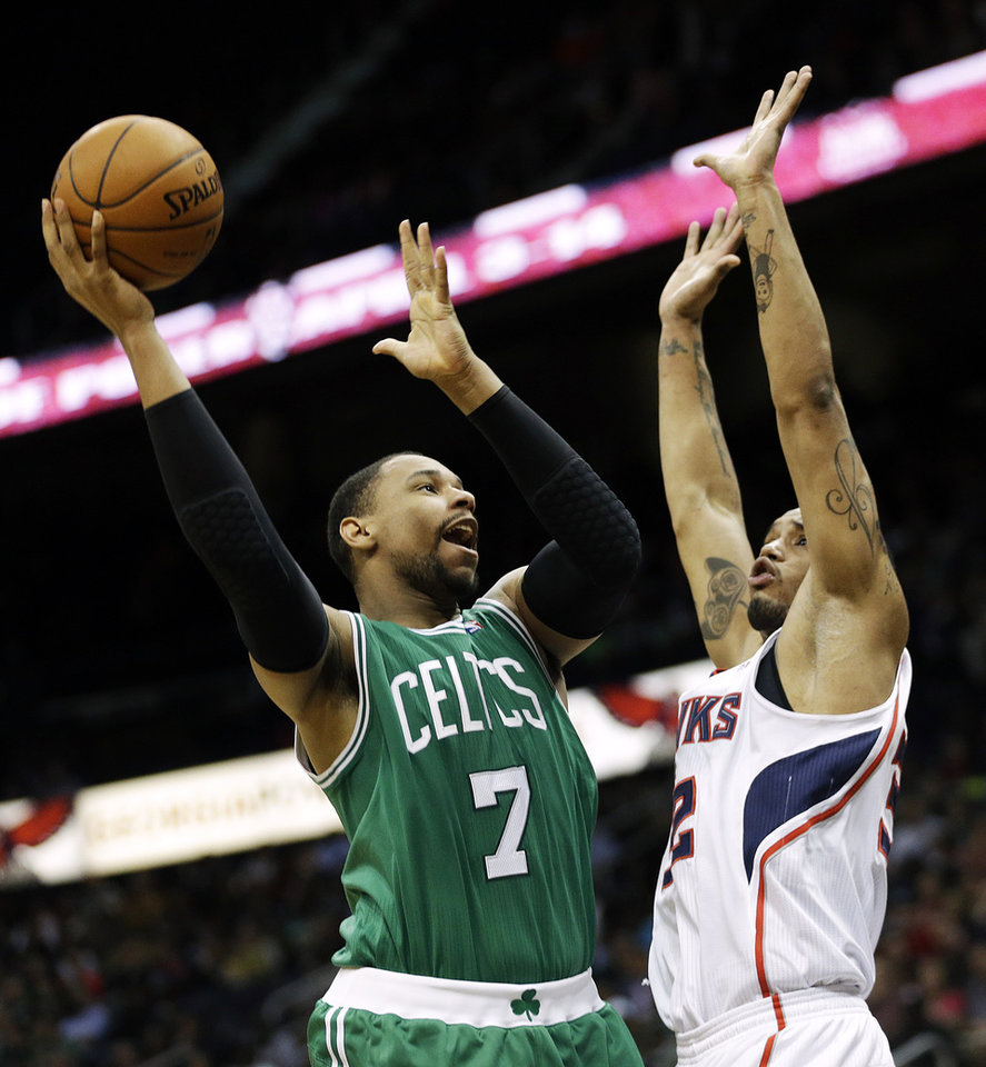 Photo - Boston Celtics' Jared Sullinger, left, puts up a shot against Atlanta Hawks' Mike Scott in the fourth quarter of an NBA basketball game, Wednesday, April 9, 2014, in Atlanta. The Hawks won 105-97. (AP Photo/David Goldman)