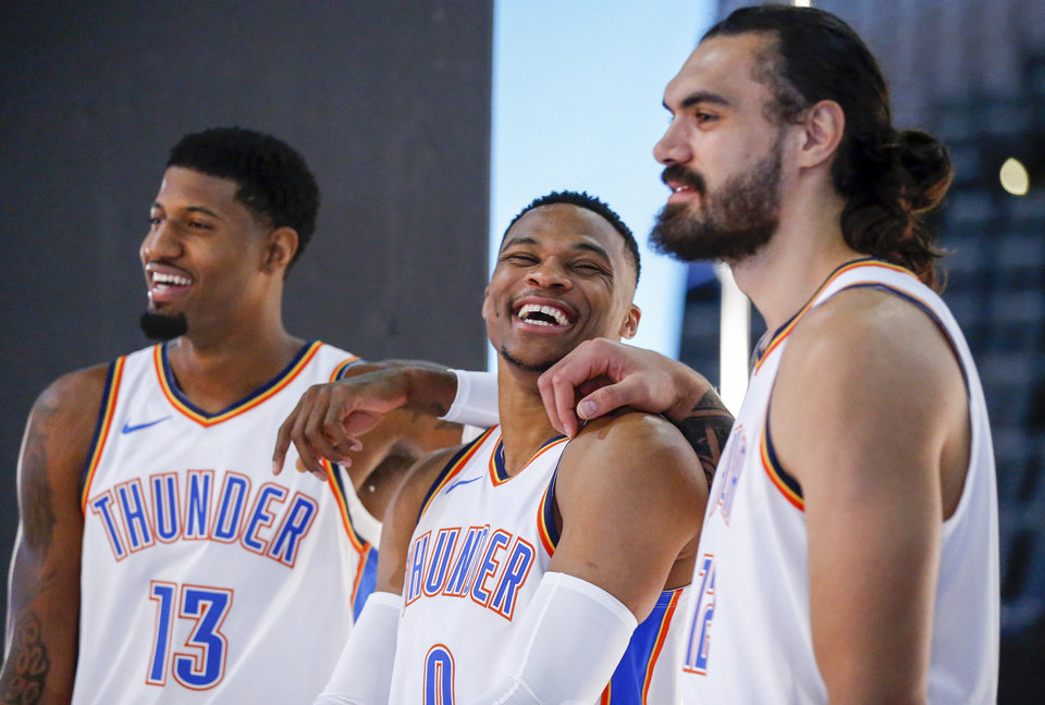 Photo - Russell Westbrook laughs between teammates Paul George, left, and Steven Adams while waiting to take a photo during media day for the Oklahoma City Thunder at Chesapeake Energy Arena in Oklahoma City, Monday, Sept. 24, 2018. Photo by Nate Billings, The Oklahoman