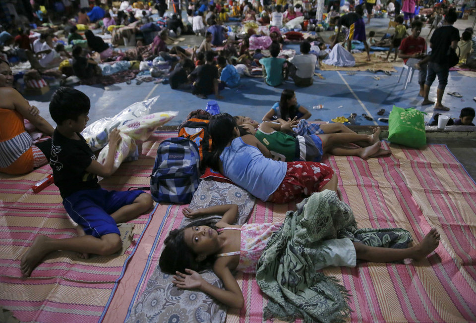 Photo - Typhoon evacuees are housed at a school gymnasium after fleeing their homes due to flooding brought by Typhoon Koppu in Cabanatuan city in northern Philippines Monday, Oct. 19, 2015. The slow-moving typhoon blew ashore with fierce wind in the northeastern Philippines early Sunday, toppling trees and knocking out power and communications and forcing the evacuation of thousands of villagers. Koppu weakened once on land, and by Monday afternoon, Koppu had weakened into a tropical storm over Ilocos Norte province with winds of 105 kilometers (65 miles) per hour and gusts of up to 135 kph (84 mph). (AP Photo/Bullit Marquez)