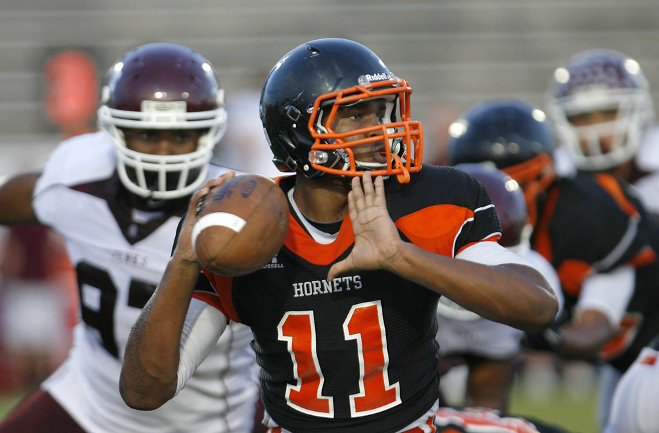 Photo - Booker T. Washington quarterback prospect Dominique Alexander passes under pressure from the Jenks defense during a scrimmage at Booker T. Washington High School in Tulsa on Friday, August 19, 2011. MATT BARNARD/Tulsa World