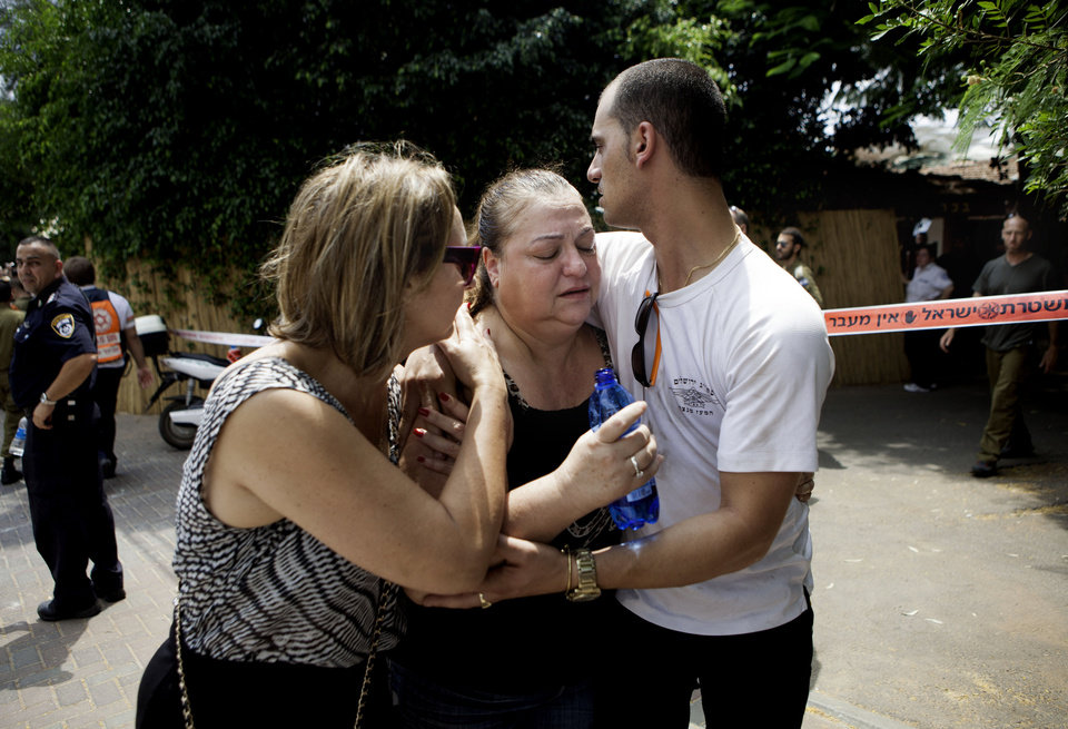 Photo - Israelis try to comfort a woman overcome by emotion after a rocket was fired by Palestinians militants from Gaza, in Yahud, central Israel, Tuesday, July 22, 2014. Israel has said its campaign, launched July 8, is aimed at stopping Hamas rocket fire into Israel — some 2,000 rockets have been launched over the past two weeks, the military says — and destroying tunnels the military says Hamas has constructed from Gaza into Israel for attacks against Israelis. (AP Photo/Dan Balilty)