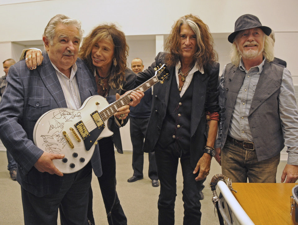 Photo - FILE - In this Oct. 8, 2013 file photo released by Uruguay's Press Office, President Jose Mujica, left, poses with Aerosmith's band members Steven Tyler, second from left, Joe Perry, second from right, and Brad Whitford after receiving an autographed guitar as a gift at presidential house in Montevideo, Uruguay. While outside his country he is an international figure, well known for his modest lifestyle, consistent with his ideals and his good-nature, among his own people Uruguay's President known as