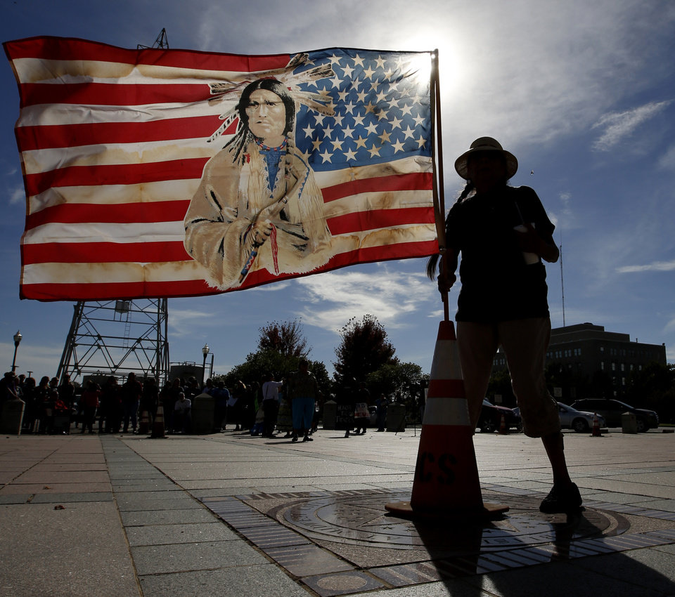 Photo -  Jennell Downs, with the Kickapoo Tribe of Oklahoma, puts up a flag Monday at the state Capitol in Oklahoma City during a protest against the Dakota Access Pipeline. Photo by Steve Gooch, The Oklahoman]