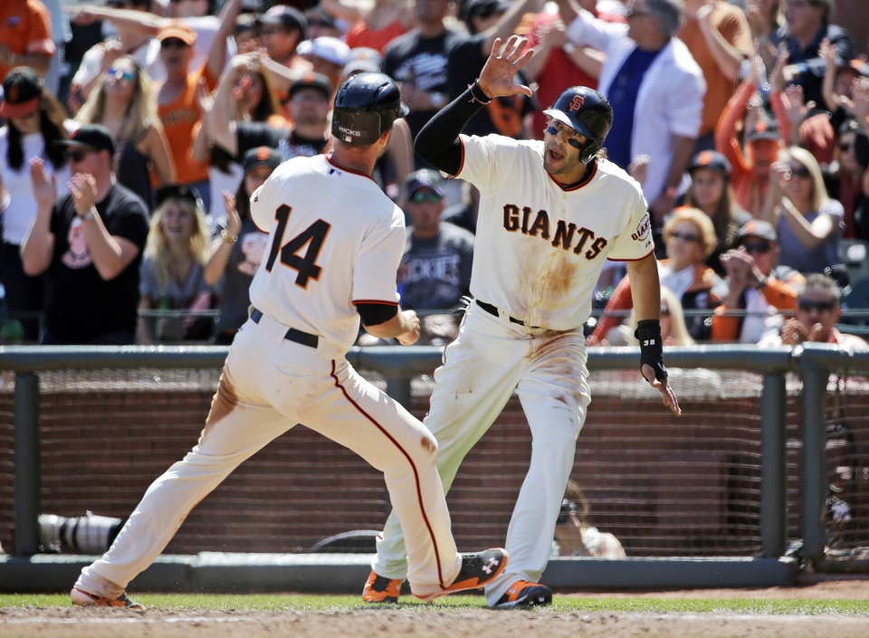 Photo - San Francisco Giants' Brandon Hicks, left, and Michael Morse celebrate after being driven in with a single from teammate Angel Pagan during the fifth inning of a baseball game against the Colorado Rockie on Sunday, April 13, 2014, in San Francisco. (AP Photo/Marcio Jose Sanchez)