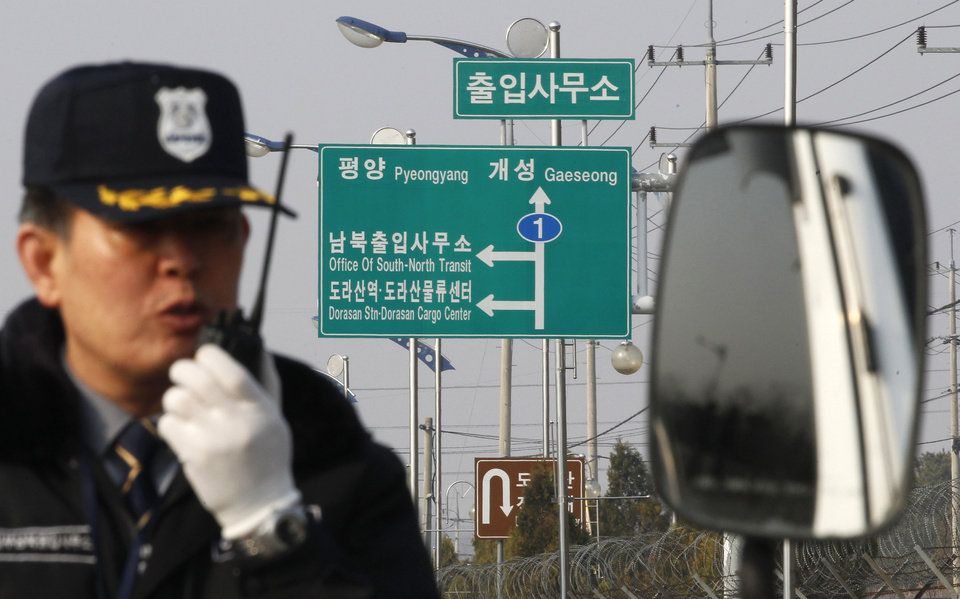 Photo - A South Korean security guard works to turn back vehicles as they were refused to enter to Kaesong, North Korea, at the customs, immigration and quarantine office in Paju, South Korea, near the border village of Panmunjom, Thursday, April 4, 2013. North Korea on Wednesday barred South Korean workers from entering a jointly run factory park just over the heavily armed border in the North, officials in Seoul said, a day after Pyongyang announced it would restart its long-shuttered plutonium reactor and increase production of nuclear weapons material. (AP Photo/Ahn Young-joon)