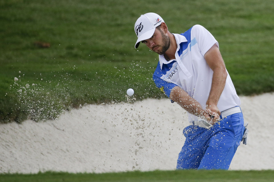 Photo - Troy Merritt hits out of the sand and onto the 16th green during the third round of the St. Jude Classic golf tournament Sunday, June 8, 2014, in Memphis, Tenn. Merritt made par on the hole. Weather delays during the week forced Saturday's third round to be finished Sunday morning before the final round could begin. (AP Photo/Mark Humphrey)