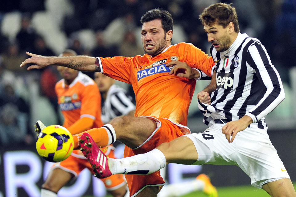 Photo - Juventus forward Fernando Llorente, of Spain,  challenges for the ball with Udinese' defender Maurizio Domizi during a Serie A soccer match between Juventus and Udinese at the Juventus stadium, in Turin, Italy, Sunday, Dec. 1, 2013. (AP Photo/Massimo Pinca)