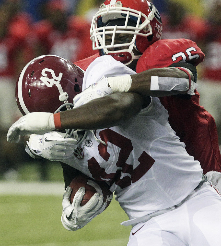 Photo - Alabama running back Eddie Lacy (42) is hit by Georgia safety Shawn Williams (36) during the first half of the Southeastern Conference championship NCAA college football†game, Saturday, Dec. 1, 2012, in Atlanta. (AP Photo/Jamie Martin)