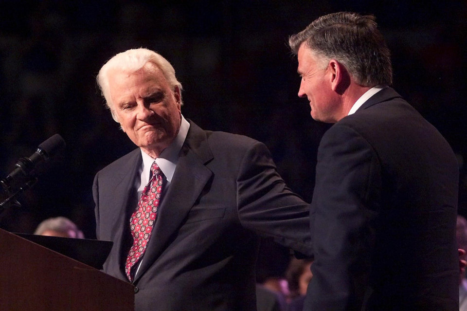 Photo - Mission Oklahoma City Friday, June 13, 2003 downtown  at the Ford Center featuring Rev. Billy Graham. Rev Billy Graham's reaches back to sqeeze his son Franklin's arm after he introduced him.  Staff photo by Doug Hoke.