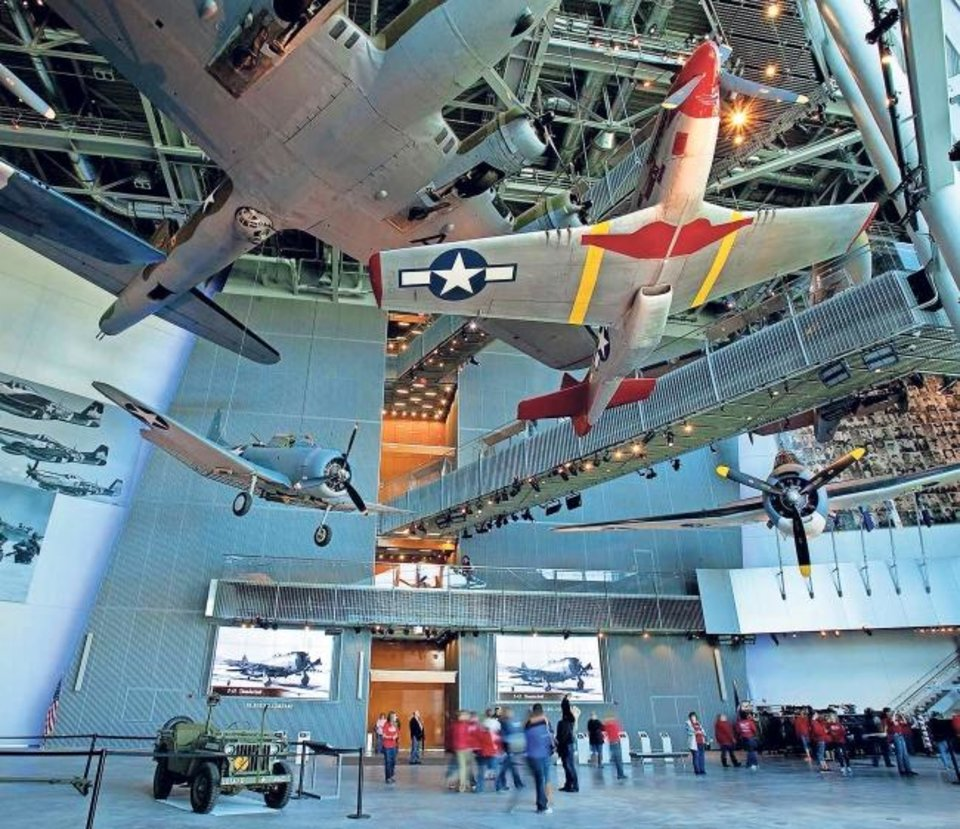 Photo -  A North American P-51 Mustang (with red markings) and other squadron planes soar in the lobby of The National WWII Museum in New Orleans. [Provided]