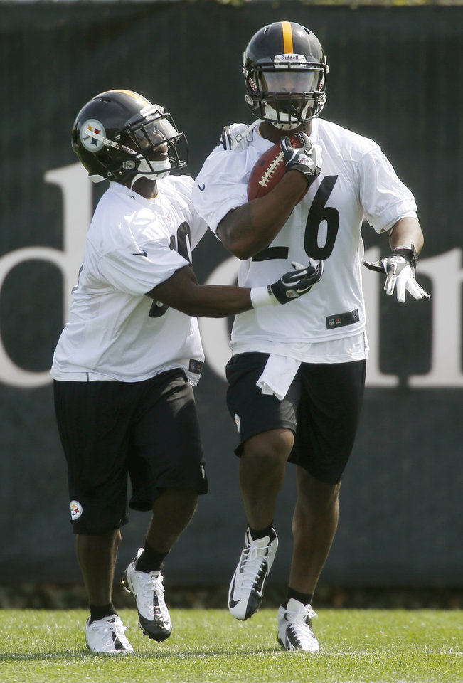 Photo - Pittsburgh Steelers second round draft pick running back Le'Veon Bell, right, gets poked at by free agent running back Curtis McNeal from Southern California, during ball retention drills at the NFL football rookie minicamp on Friday, May 3, 2013 in Pittsburgh. (AP Photo/Keith Srakocic)