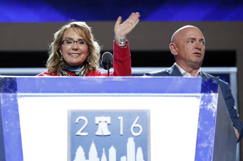 Photo - Former Rep. Gabby Giffords, D-Ariz, waves from the podium as her husband Astronaut Mark Kelly (ret.) looks on during a sound check before the start of the first day session of the Democratic National Convention in Philadelphia, Monday, July 25, 2016. (AP Photo/Carolyn Kaster)