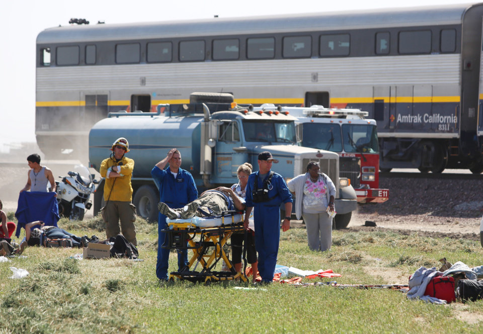 Emergency personnel respond to the scene of a train derailment where authorities say at least 20 passengers suffered minor to moderate injuries when a big rig truck collided with a southbound Amtrak train in the central valley Monday, Oct. 1, 2012 in Hanford, Calif. (AP Photo/The Fresno Bee, Gary Kazanjian)