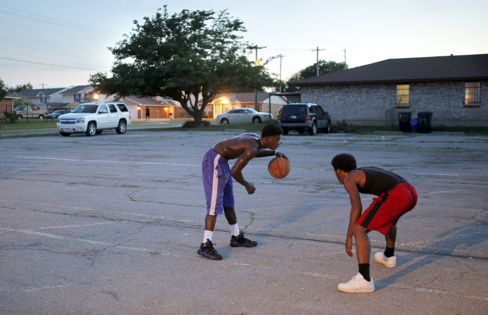 Photo - Quasean Sims dribbles up court as Trenzell Griffin defends during midnight basketball at Christ Temple Community Church in Oklahoma City, Friday, Aug. 1, 2014. Photo by Sarah Phipps, The Oklahoman