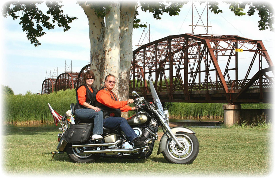 """Ron and Ann Sipes from Midwest City are members of the Star Chapter 378 Touring and Riding Motorcycle Association\'s north OKC chapter. They are posing at our first portrait photo shoot with the historic steel cantilever bridge and a section of the original Mother Road, Route 66 at Lake Overholser in the background. The theme for this event is """"It\'s not the destination that counts, It\'s the journey"""". Community Photo By: Garry Baird Submitted By: Garry, Oklahoma City"""