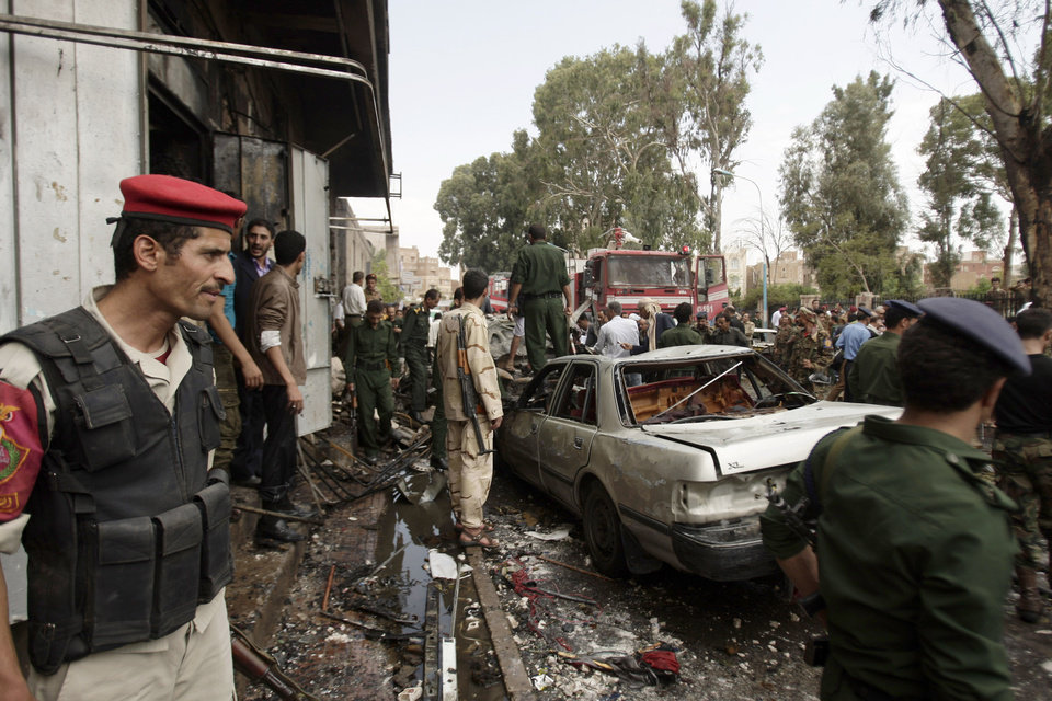 Photo -   Yemeni soldiers gather at the site of a car bomb attack targeting the motorcade of the country's defense minister in Sanaa, Yemen, Tuesday, Sept. 11, 2012. Yemeni officials say a car bomb targeting the motorcade of the country's defense minister has killed several people, but the minister escaped unharmed. (AP Photo/Hani Mohammed)