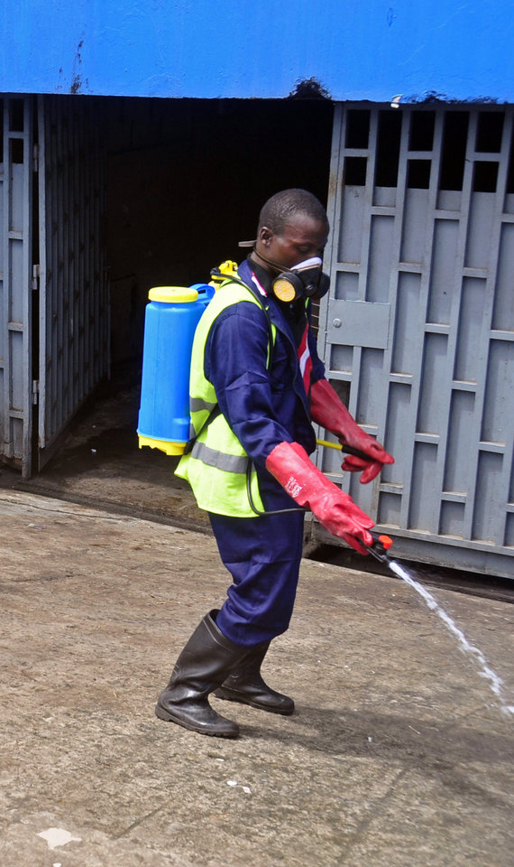 Photo - A employee  of the Monrovia City Corporation spray disinfectant on a street in front of a building in a bid to prevent the spread of  the deadly Ebola virus, in the city of Monrovia, Liberia, Friday, Aug. 1, 2014. U.S. health officials warned Americans not to travel to the three West African countries hit by the worst recorded Ebola outbreak in history. The travel advisory issued Thursday applies to nonessential travel to Guinea, Liberia and Sierra Leone, where the deadly disease has killed more than 700 people this year. (AP Photo/Abbas Dulleh)