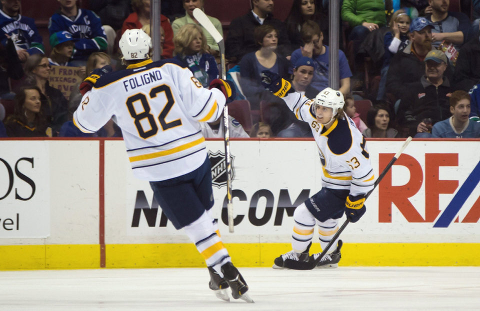 Photo - Buffalo Sabres' Tyler Ennis, right, celebrates his goal against the Vancouver Canucks as teammate Marcus Foligno skates to join him during first period NHL hockey action in Vancouver, British Columbia, on Sunday March 23, 2014. (AP Photo/The Canadian Press, Darryl Dyck)