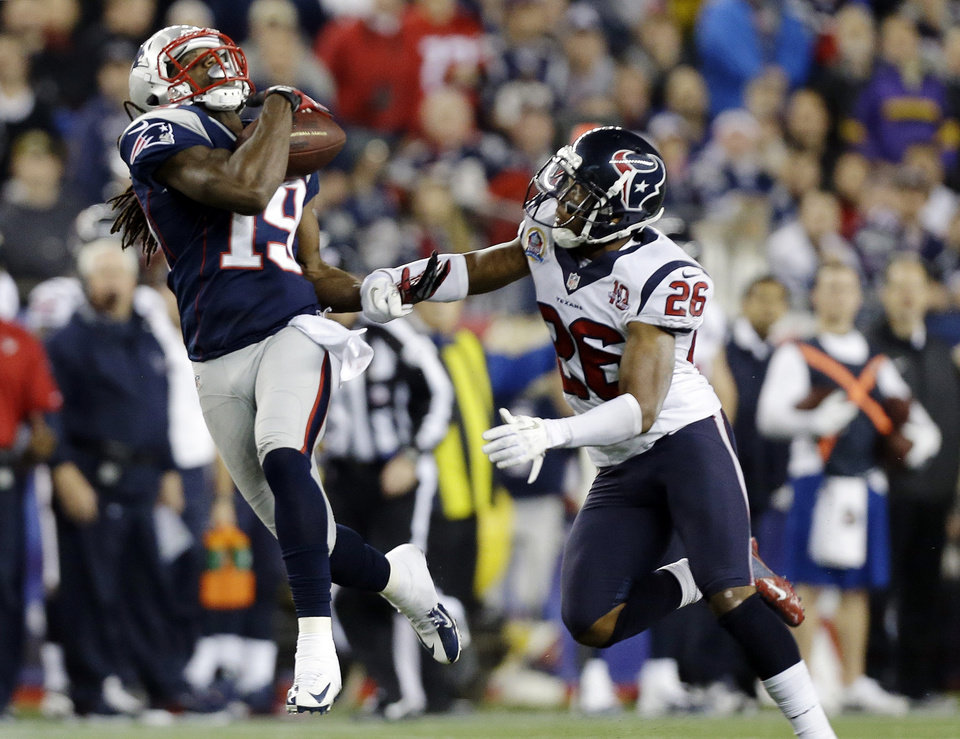 Photo - New England Patriots wide receiver Donte' Stallworth (19) catches a pass in front of Houston Texans defensive back Brandon Harris (26) before running it in for a touchdown during the third quarter of an NFL football game in Foxborough, Mass., Monday, Dec. 10, 2012. (AP Photo/Elise Amendola)