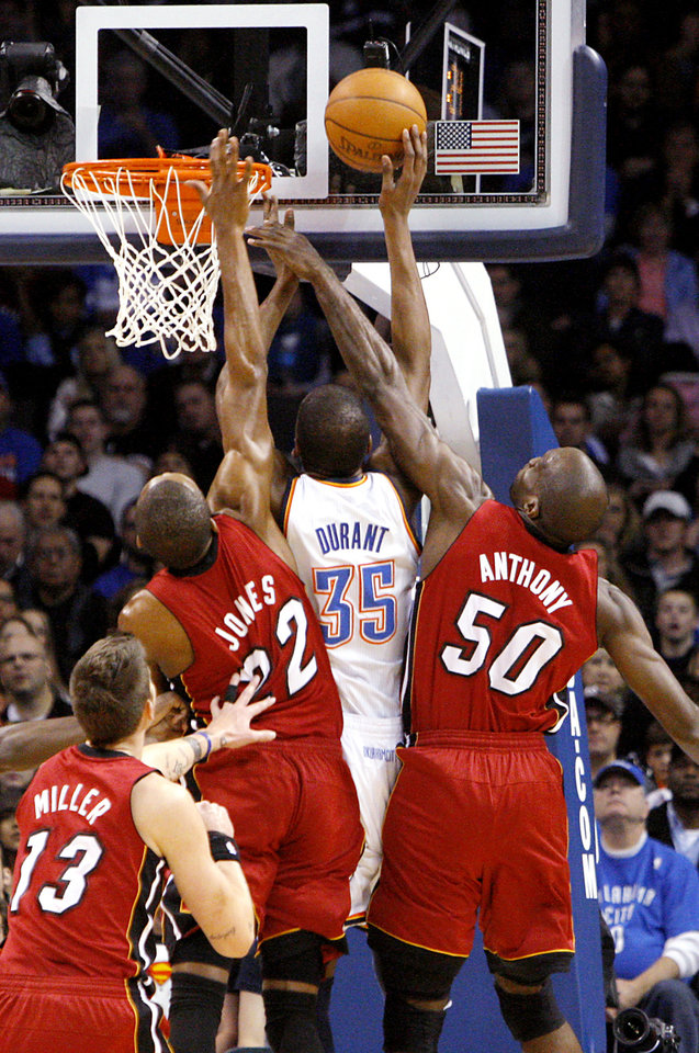 Photo - Oklahoma City's Kevin Durant is defended by Miami's Mike Miller, Joel Anthony, and James Jones during their NBA basketball game at the OKC Arena in Oklahoma City on Thursday, Jan. 30, 2011. Photo by John Clanton, The Oklahoman